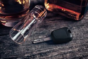 Car keys and fallen empty glass on the table