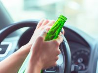 Person holds beer bottle while driving