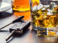 Car keys and glass of alcohol on table in pub or restaurant.