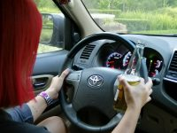 woman driving while holding a beer