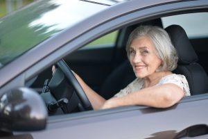 Portrait Of Smiling Senior Woman Driving Car - dangers of elderly drivers blog post
