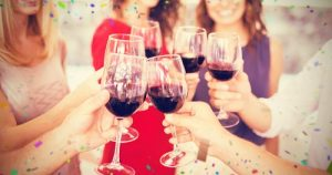 group of women holding up wine glasses with red wine in them.